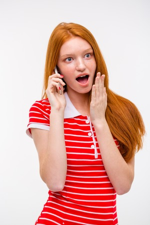 shoked: Amazed excited pretty attractive redhead woman with long hair talking on mobile phone
