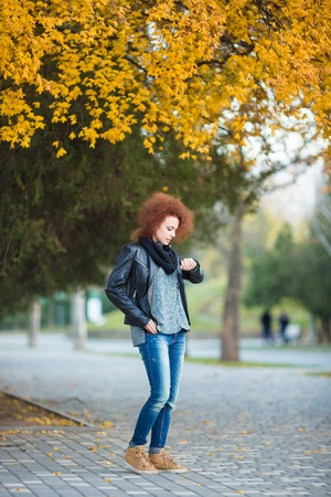 somebody: Full length portrait of a young woman waiting somebody and looking on wrist watch outdoors in park