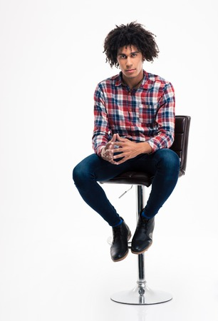 joy: Full length portrait of a young man sitting on the chair isolated on a white background