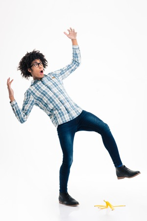 banana skin: Full length portrait of a young afro american man slipping on banana skin isolated on a white background
