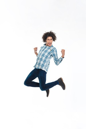 afro hairdo: Full length portrait of a cheerful afro american man jumping isolated on a white background