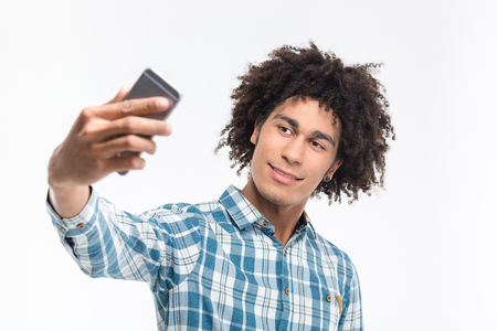Portrait of a happy afro american man making selfie photo on smartphone isolated on a white background Stock Photo