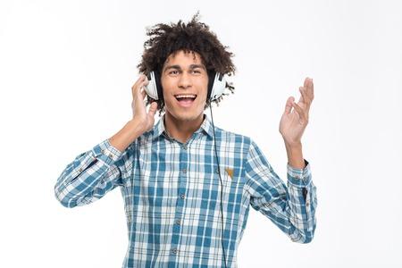cabello rizado: Retrato de hombre afroamericano alegre con música que escucha el pelo rizado en los auriculares aislados en un fondo blanco