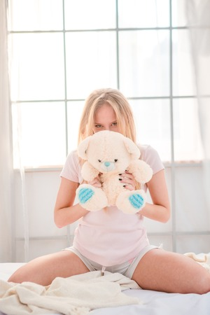 blonde teenager: Portrait of a young woman sitting with teddy bear on the bed at home