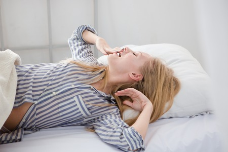 striped pajamas: Young pretty beautiful woman in striped pajamas yawning and stretching herself lying in her white bed in the morning