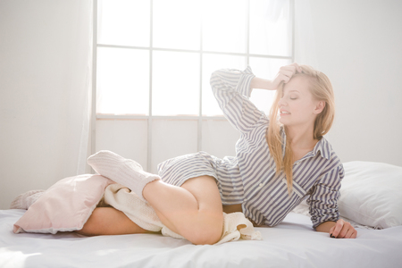Attractive playful young female with blonde hair in striped shirt and knitted socks lying and touching her blonde hair