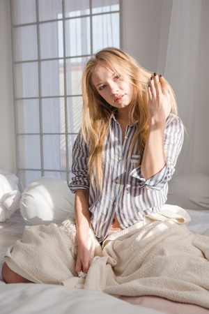 bedcover: Lovely charming young woman sitting on white bed and touching her blonde hair Stock Photo