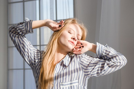 striped pajamas: Young sleepy tired fatigued woman in striped pajamas stretching with closed eyes Stock Photo