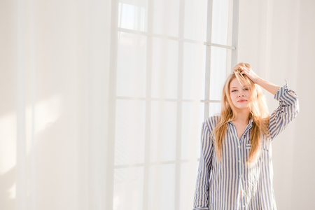 striped pajamas: Carefree relaxed beautiful young female with tousled hair in striped pajamas standing near big window Stock Photo
