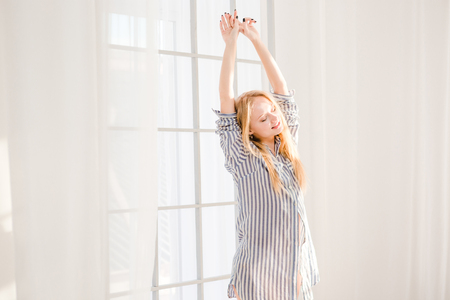 pleased: Smiling pleased sleepy blonde woman in striped pajamas waking up and stretching near big window