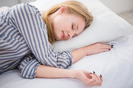 striped pajamas: Pretty blonde young woman sleeping in her white bed on the pillow in striped pajamas
