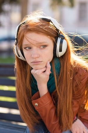 long red hair woman: Portrait of beautiful sad pensive young woman with long red hair in headphones sitting in the park Stock Photo