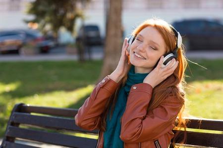personas escuchando: Contenido mujer joven alegre en la chaqueta de cuero y bufanda sentado en el banco en el parque y escuchar música con los ojos cerrados Foto de archivo