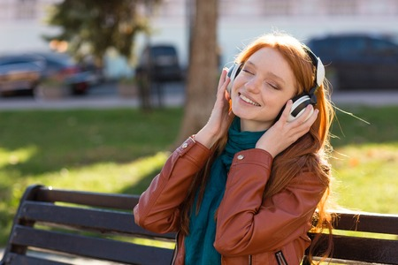 listening music: Content cheerful young woman in leather jacket and scarf sitting on bench in park and listening to music with eyes closed Stock Photo