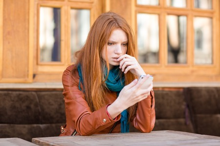 shoked: Embarrassed sad shoked young redhead lady reading message in mobile phone sitting in open air cafe Stock Photo
