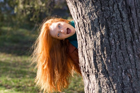 peep out: Amusing funny girl with beautiful long red hair looking out from the tree in park