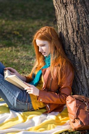 pelirrojas: chica inteligente concentrado con el pelo largo de color rojo que lee un libro bajo el �rbol en parque Foto de archivo