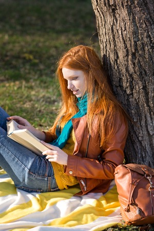 redhead girl: Concentrated smart girl with long red hair reading a book under the tree in park