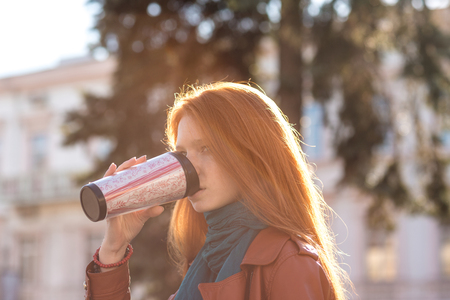 Beautiful redhead young lady with long hair in leather jacket and scarf drinking coffee from tumbler Stock Photo