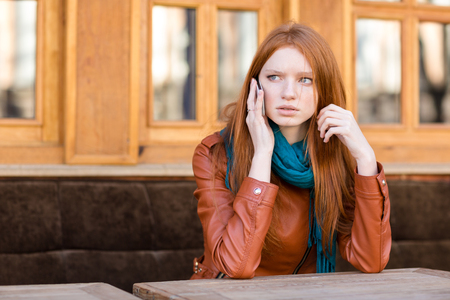 concerned: Worried concerned young redhead woman in leather jacket and scarf talking on cellphone in outdoor cafe