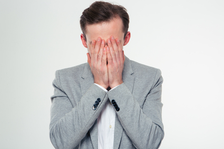 worried executive: Portrait of a stressed businessman covering her face with palms isolated on a white background Stock Photo