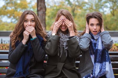 ベンチに座っていると感覚を表す 3 人の女性の肖像画: ミュート、視覚障害者、聴覚障害者の屋外 写真素材