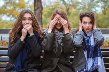 representing: Portrait of a three women sitting on the bench and representing senses: mute, blind and deaf outdoors