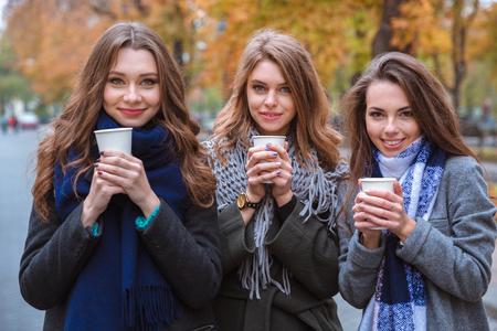 niñas sonriendo: Retrato de un tres hermosas mujeres de tomar café al aire libre