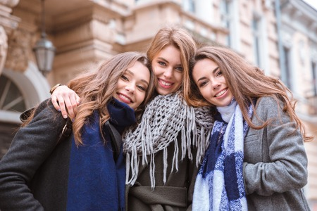 three friends: Portrait of a three smiling girlfriends standing together outdoors with old building on background