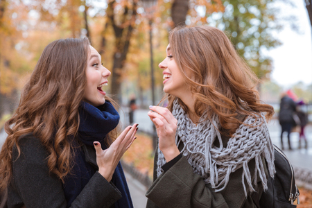 sister: Portrait of a two laughing women talking outdoors in autumn park