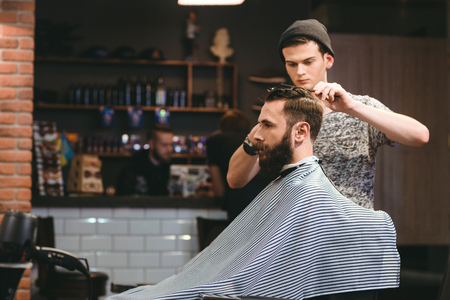 Young handsome barber making haircut of attractive bearded man in barbershop Archivio Fotografico