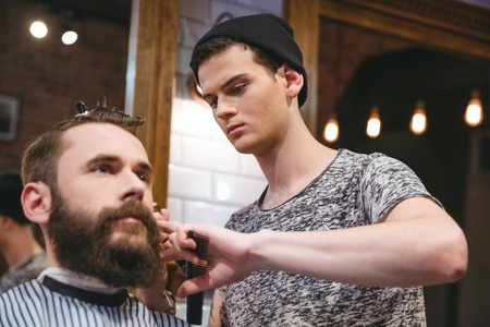 skillful: Young skillful barber making haircut to handsome bearded man in barbershop
