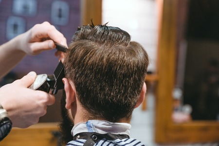 short haircut: Closeup of barbers hands making short haircut to man using trimmer in barbershop Stock Photo
