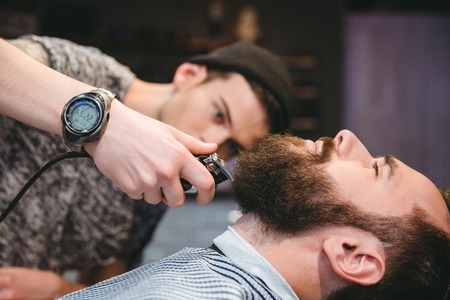 hair clippers: Attractive bearded man getting his beard shaved by modern barber in barber shop