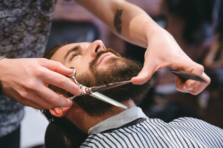 haircut: Hairdresser doing haircut of beard using comb and scissors to young attractive man in mens hair salon