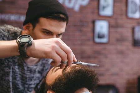 barber scissors: Closeup of young consentrated barber grooming beard of handsome man with scissors at barber shop
