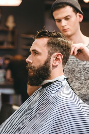 Professional hairdresser cutting young bearded mans hair in hairdressing salon