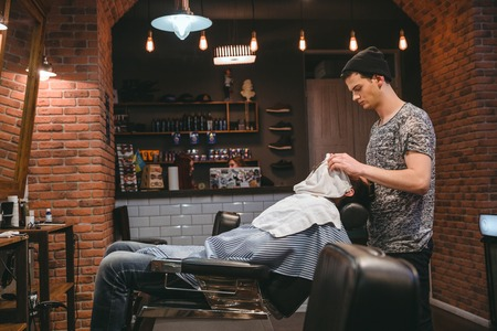 hairdressers shop: Barber finishing grooming and taking care of clients face in barbershop