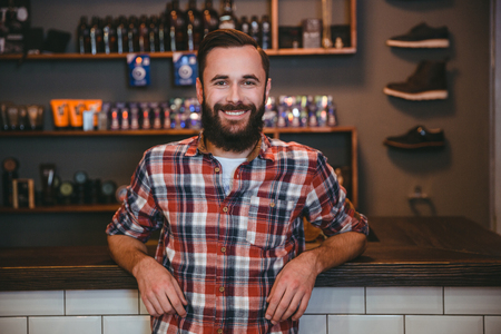 men standing: Happy cheerful satisfied man with beard in plaid shirt in barbershop after visiting barber Stock Photo