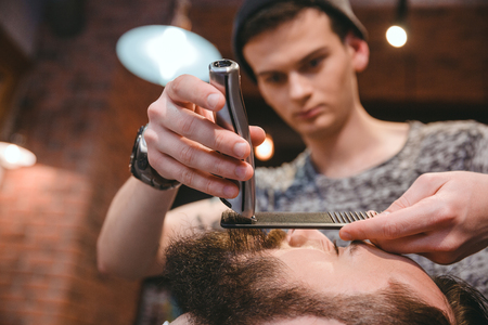 hair clippers: Young concentrated skillful barber making perfect beard to handsome bearded man using trimmer and comb in hair salon Stock Photo