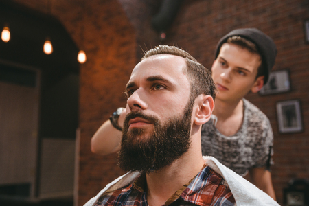 Modern barber in black hat combing hair of client with beard at barbershop