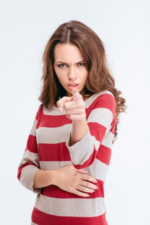 accusing: Portrait of a young angry woman pointing finger at camera isolated on a white background Stock Photo