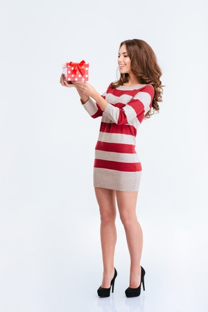 anniversary sexy: Full length portrait of a smiling woman in dress holding gift box isolated on a white background