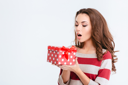 Portrait of a young amazed woman holding gift box isolated on a white background Stock Photo