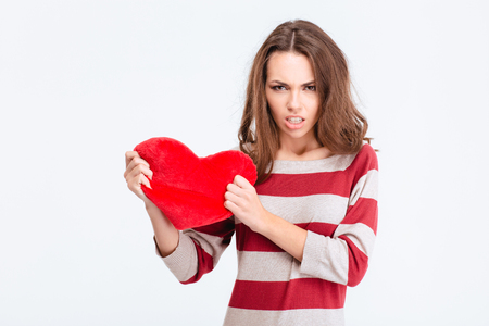 half face: Portrait of a young angry woman holding red heart isolated on a white background