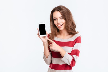 Portrait of a cheerful cute woman showing blank smartphone screen isolated on a white background Stock Photo