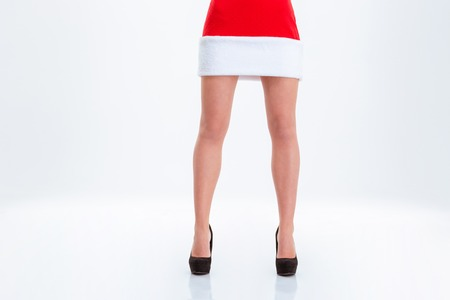 piernas con tacones: Closeup portrait of a sexy female legs in santa claus cloth isolated on a white bakground