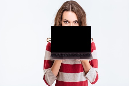 covering face: Portrait of a young woman covering face with blank laptop computer screen isolated on a white background Stock Photo