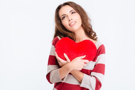 cute teen girl: Портрет счастливого вдумчивый женщина держит красное сердце и глядя вверх, изолированные на белом фоне Фото со стока