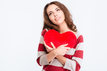 cute lady: Portrait of a happy thoughtful woman holding red heart and looking up isolated on a white background Stock Photo